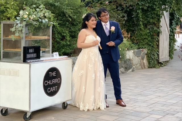 bride and groom at churro cart